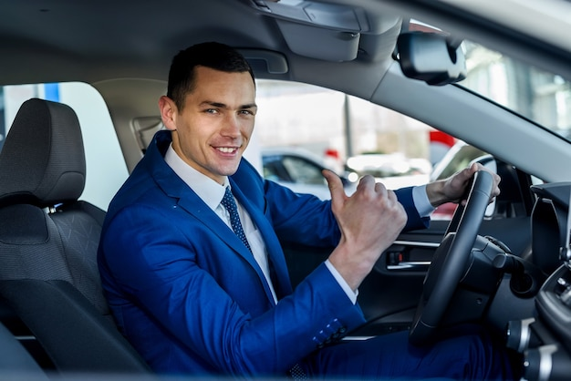 Junger und glücklicher geschäftsmann, der im neuen auto im ausstellungsraum sitzt