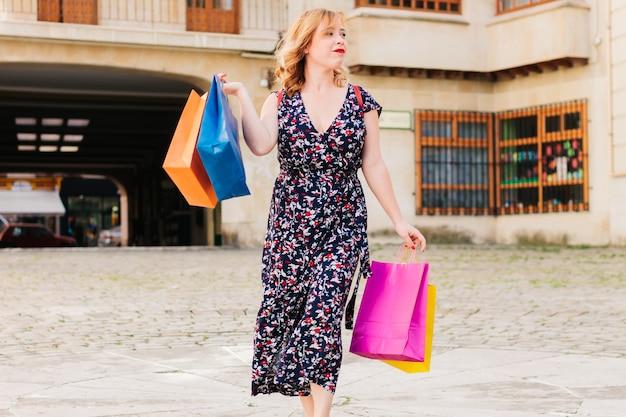 Junger und glücklicher shopper mit bunten wiederverwendbaren papiertüten. verkaufssaison am black friday.