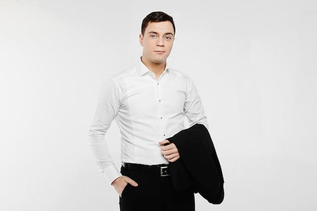 Junger und gutaussehender geschäftsmann im weißen hemd und in der dunklen hose, die blazer auf seiner hand halten und über weißem hintergrund aufstellen, isolieren.