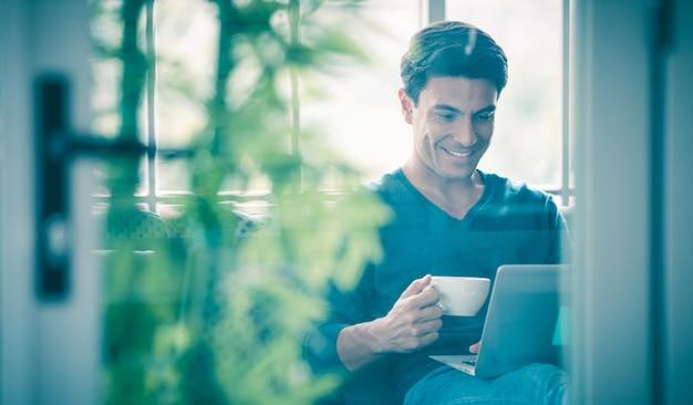Junger und gutaussehender kaukasischer geschäftsmann, der beiläufiges tuch trägt, das glücklich auf sofa sitzt, tasse hält und kaffee trinkt und laptop-notebook-computer verwendet. idee für die arbeit zu hause, videoanruf-job.