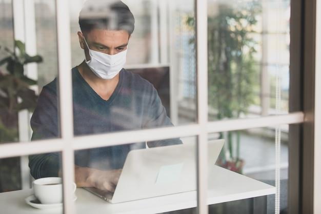 Junger und gutaussehender kaukasischer geschäftsmann mit medizinischer hygieneschutzmaske, der im haus sitzt, kaffee trinkt und einen laptop-notebook-computer verwendet. idee für die arbeit von zu hause aus in der coronavirus-krise.