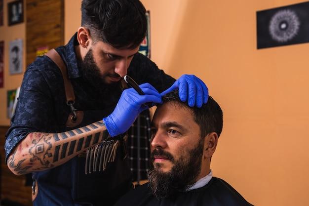 Junger und hübscher friseur, der einem männlichen kunden im salon einen neuen haarschnitt gibt.