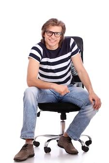 Junger und hübscher kerl, der auf dem stuhl sitzt