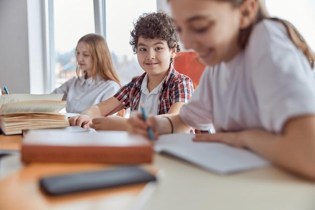 Junger und lockiger schuljunge, der auf schreibtisch sitzt und lächelt. grundschulkinder sitzen auf schreibtischen und lesen bücher im klassenzimmer.