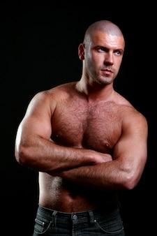 Junger und muskulöser mann auf schwarzem