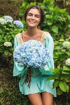 Junger und schöner frauenflorist, der hortensienblumen auf dem feld sammelt