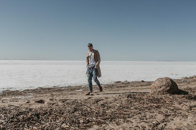 Junger und schöner junger mann, der entlang des kalten winterstrandes in einem beigen trenchcoat geht