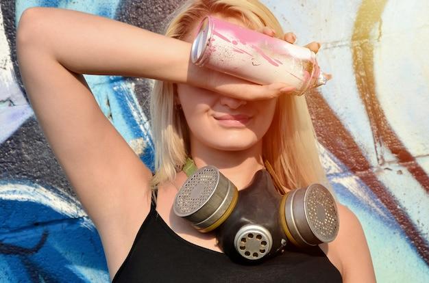 Junger und schöner lächelnder sexy mädchen graffitikünstler mit gasmaske auf ihrem hals, der seine augen mit einer spraydose steht auf einer wand versteckt
