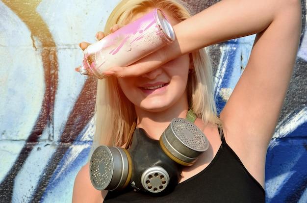 Junger und schöner lächelnder sexy mädchengraffitikünstler mit gasmaske auf ihrem hals, der seine augen versteckt
