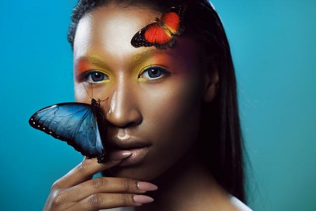 Junger und schöner schwarzer modell exotischer blick mit hellblauem schmetterling