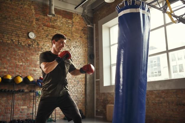 Junger und sportlicher mann, der in handschuhen in einem fitnessstudio im loft-stil boxt. boxer. profisport
