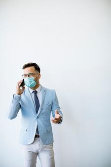 Junger und stilvoller geschäftsmann mit gesichtsmaske steht an der wand im büro und unter verwendung des mobiltelefons