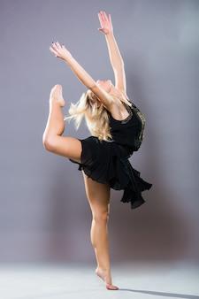 Junger und stilvoller tänzer, der auf grauem hintergrund aufwirft