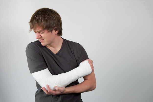 Junger unglücklicher kaukasischer mann mit gipsabdruck auf seiner hand, die unter schmerzen leidet. schuss auf einem weißen wandhintergrund.