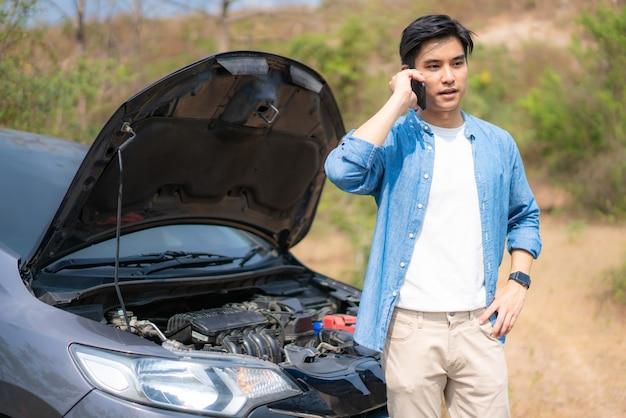 Junger unglücklicher mann, der auf einem handy vor dem kaputten auto der offenen motorhaube spricht