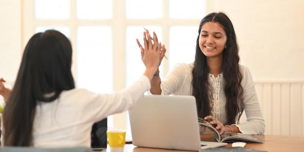 Junger universitätsstudent, der ihre lektion mit einem computer-laptop unterrichtet, während sie zusammen am holzarbeitsplatz über bequemem wohnzimmer sitzen