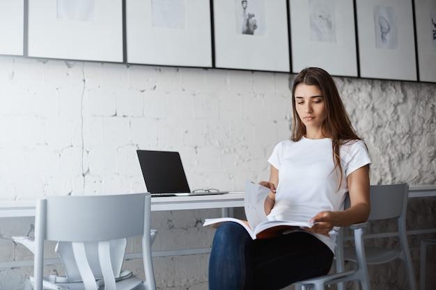 Junger universitätsstudent, der sich auf eine vorlesung vorbereitet, die arbeitsbuch liest und einen laptop benutzt.