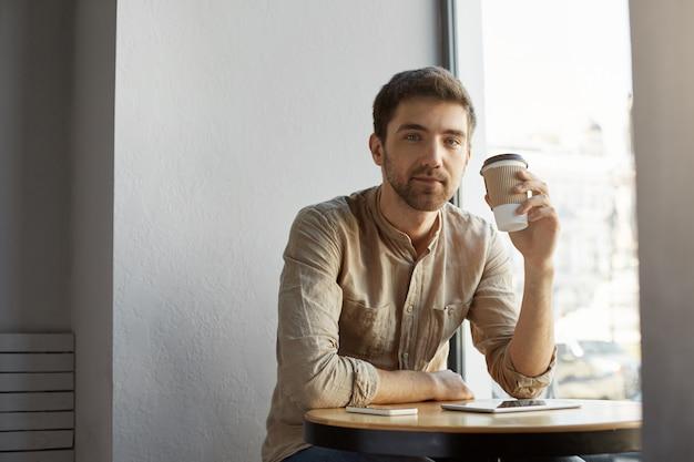 Junger unrasierter hübscher kaukasischer kerl in der freizeitkleidung, die in der cafeteria sitzt, kaffee trinkt und sich nach hartem arbeitstag ausruht.