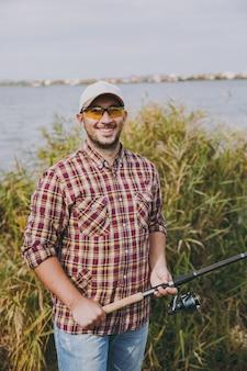 Junger unrasierter lächelnder mann in kariertem hemd, mütze und sonnenbrille hält angelrute am ufer des sees auf dem hintergrund von wasser, sträuchern und schilf. lifestyle, erholung, fischer-freizeitkonzept.