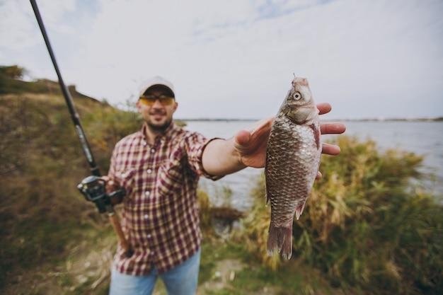 Junger unrasierter mann in kariertem hemd, mütze, sonnenbrille hält angelrute und streckt seine hand auf gefangene fische am ufer des sees in der nähe von sträuchern und schilf aus. lifestyle, erholung, freizeitkonzept für fischer
