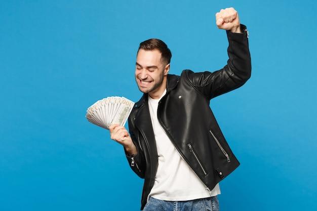 Junger unrasierter mann in schwarzer lederjacke, weißem t-shirt, das einen fan von bargeld in dollar-banknoten hält, isoliert auf blauem wandhintergrund studioporträt. menschen lifestyle-konzept. kopieren sie platz.