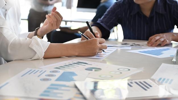 Junger unternehmensberater, der die finanzzahlen anzeigen den fortschritt analysiert.