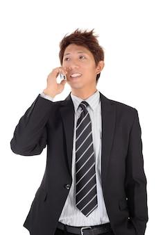 Junger unternehmer, der am telefon mit lächelndem ausdruck über weißer wand spricht.