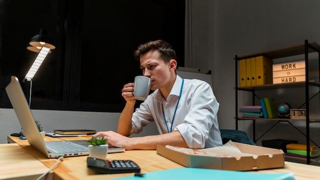 Junger unternehmer, der kaffee während der arbeit genießt