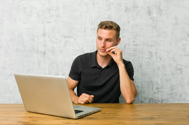 Junger unternehmer, der mit seinem laptop auf einem schreibtisch mit den fingern auf den lippen hält ein geheimnis arbeitet.