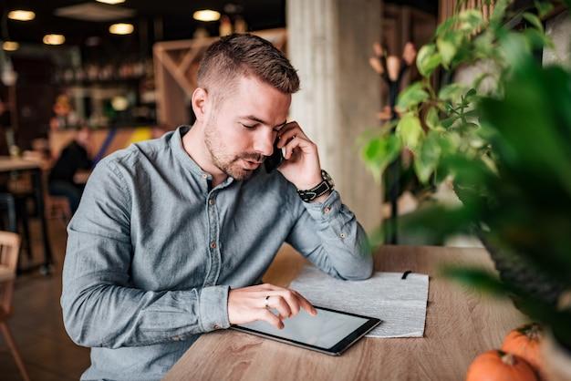Junger unternehmer, der über handy spricht und digitale tablette verwendet.