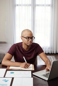 Junger unternehmer, der von zu hause aus arbeitet, dokument auf laptop liest und notizen im planer macht