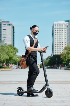 Junger unternehmer in der schutzmaske, die auf roller steht und textnachrichten auf smartphone liest