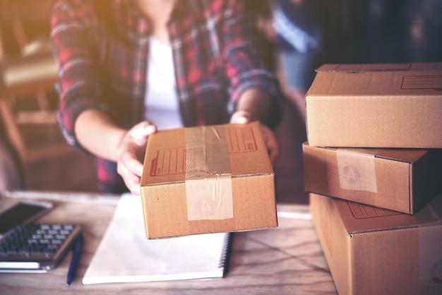 Junger unternehmer, teenagergeschäftsinhaber arbeiten zu hause, kasten für anlieferung