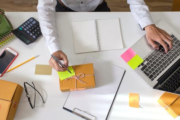 Junger unternehmermann, der laptop verwendet und adresse schreibt, um das paket dem kunden zu liefern.