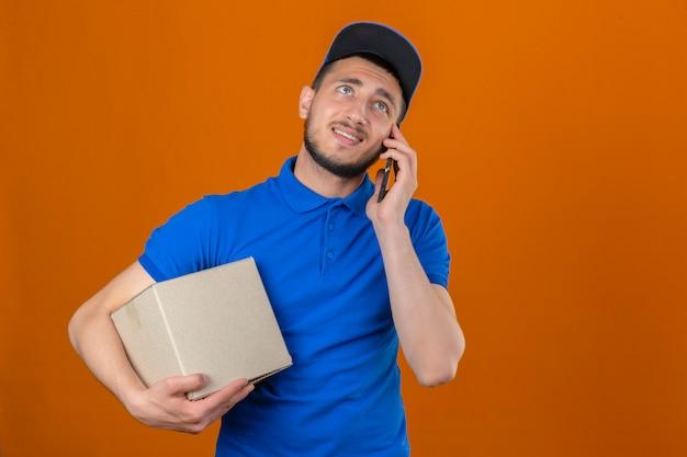 Junger unzufriedener lieferbote, der blaues poloshirt und kappe trägt, die mit pappkarton steht, der auf handy mit unglücklichem gesicht spricht, das abneigung über lokalisiertem orangefarbenem hintergrund zeigt