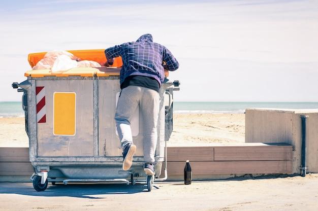 Junger vagabund, der im abfallbehälter sucht nach lebensmittel und wiederverwendbaren waren stöbert