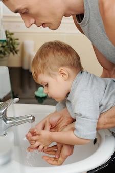 Junger vater bringt seinem kleinen sohn bei, sich im badezimmer die hände zu waschen