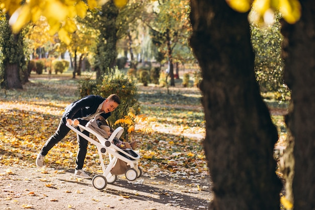 Junger vater, der mit babytochter im wagen im park geht