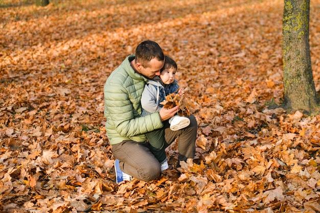 Junger vater, der mit einem kleinen kind in einem herbstpark spielt.