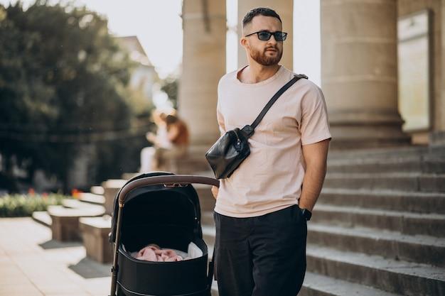 Junger vater, der mit seinem baby in einem kinderwagen hinausgeht