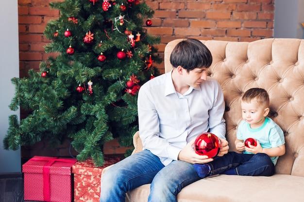 Junger vater, der mit seinem kleinen sohn auf couch nahe weihnachtsbaum spielt