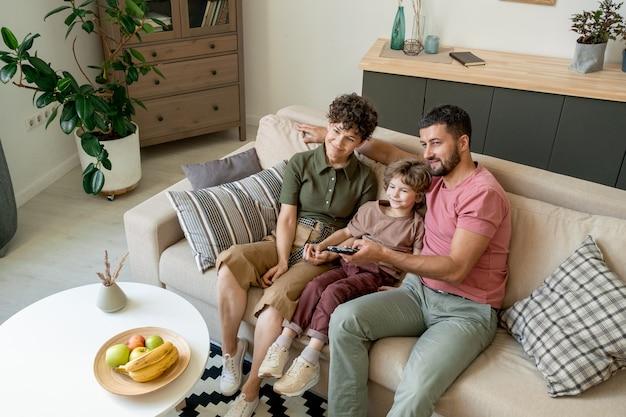 Junger vater in freizeitkleidung, der tv-kanal wählt und knopf auf fernbedienung drückt, während er von seiner frau und seinem kleinen sohn auf der couch sitzt