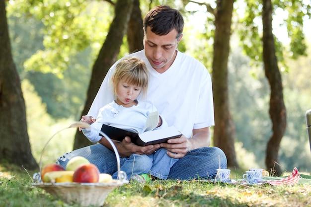 Junger vater mit einer glücklichen tochter, die die bibel auf einem picknick liest
