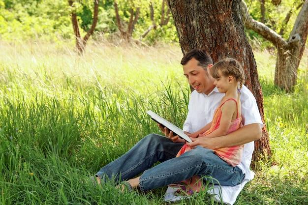 Junger vater mit einer kleinen tochter, die die bibel liest