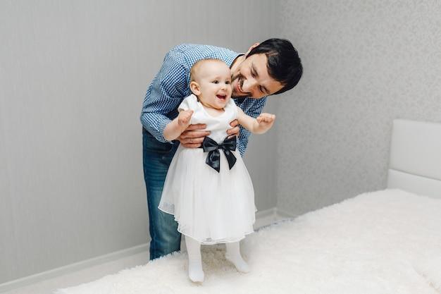 Junger vater mit ihrer kleinen tochter kleidete im weißen kleid und in der stellung auf dem bett an