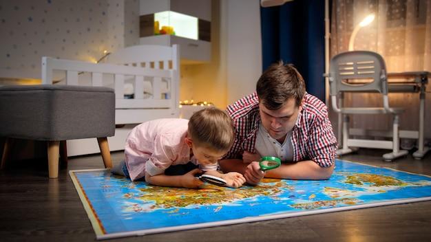Junger vater mit kleinem sohn, der die karte durch die lupe erforscht und betrachtet. konzept von reisen, tourismus und kindererziehung.