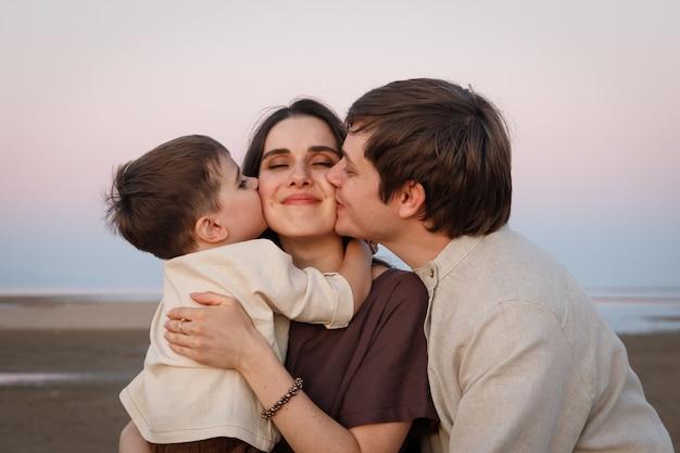 Junger vater mit seinem kleinen sohn, der seine frau und seine mutter küsst. leinenkleidung im familienlook.