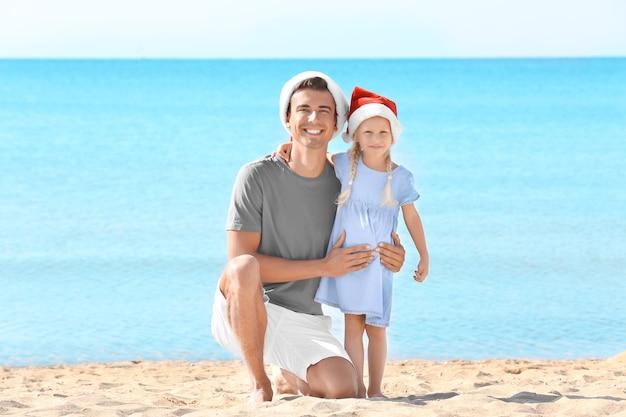 Junger vater mit süßem mädchen am strand. weihnachtsfeier konzept