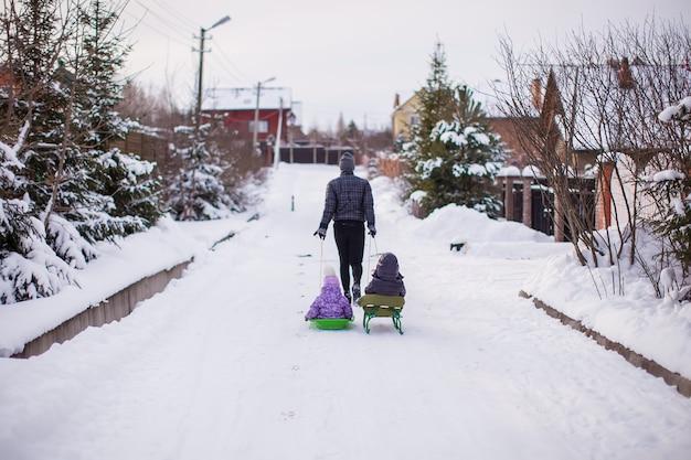 Junger vater rollt seine kleinen süßen töchter auf einem schlitten im schnee im freien