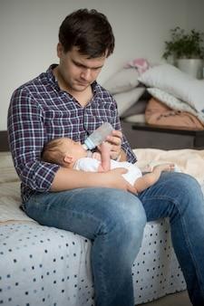 Junger vater sitzt auf dem bett und füttert seinen neugeborenen sohn